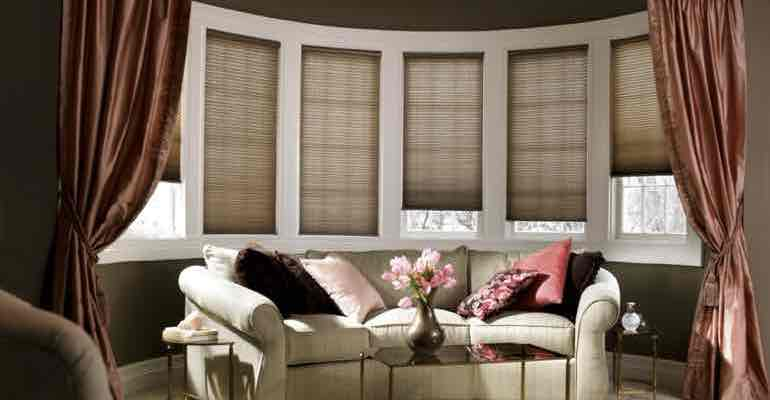 Adjustable honeycomb shades in lounge bow window.