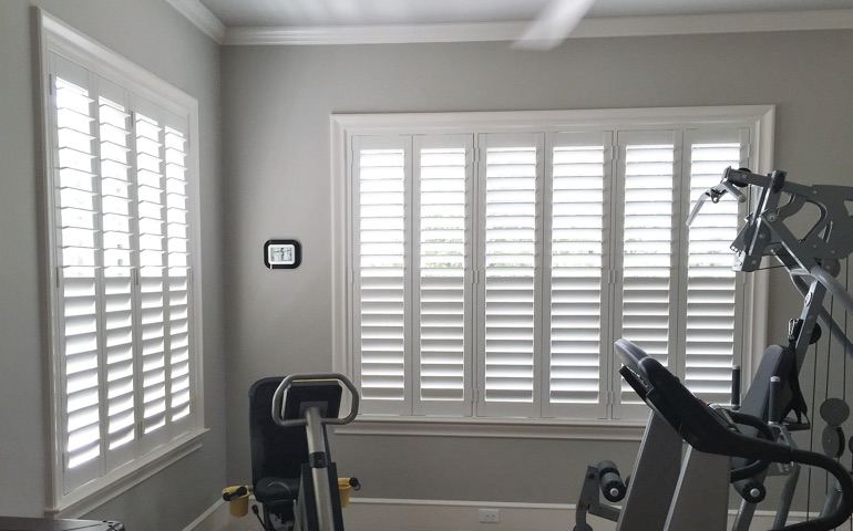 Austin home gym with shuttered windows.