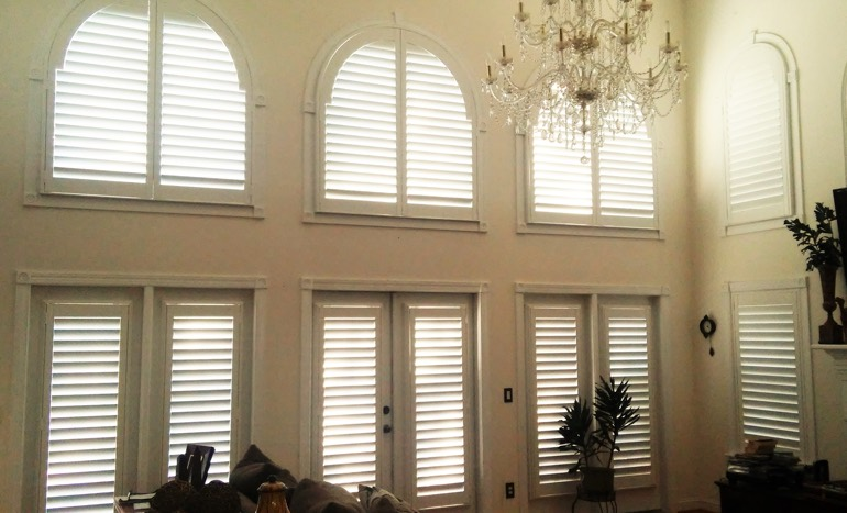 Family room in two-story Austin home with plantation shutters on high windows.