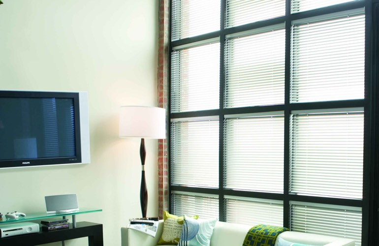 Blinds covering business window that's divided into square panes