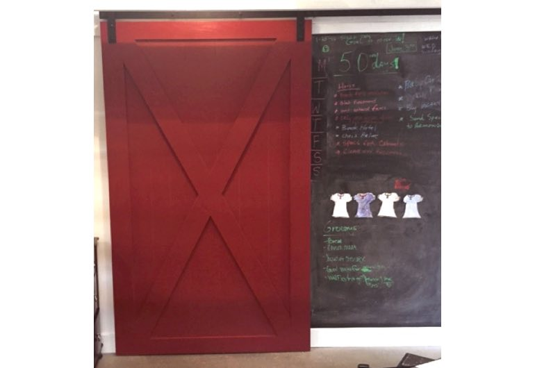 Red sliding barn door with black hardware next to chalkboard