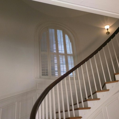 White plantation shutters adorning rounded window located in spiral stairwell.