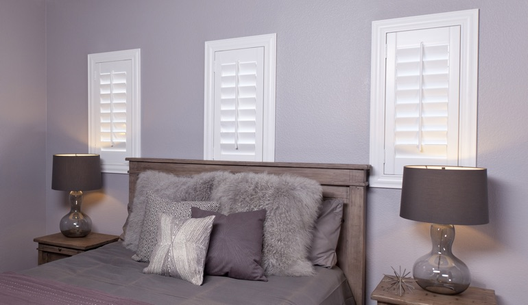 White plantation shutters in Austin bedroom windows.