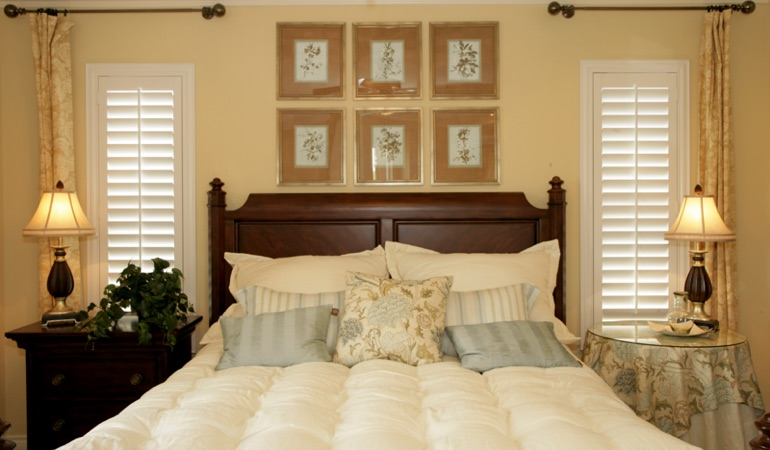 Bedroom with two tall plantation shutters on either side of bed in Austin