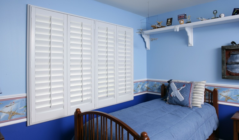 Blue kids bedroom with white plantation shutters in Austin